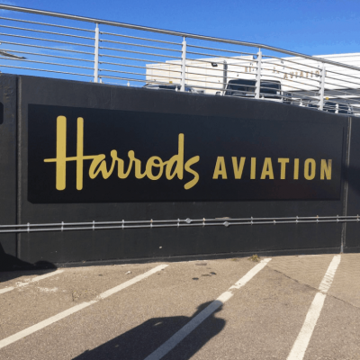 A black Harrods sign applied to a wall.