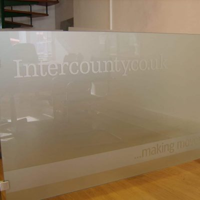 A glass barrier with metal poles featuring company logo and tagline