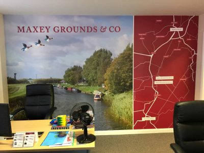 A Office with a wall mural featuring the company name a picture of a river and a map